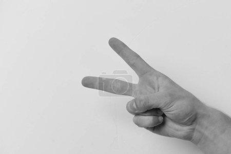 Foto de Mano masculina muestra dos dedos. Gesto de la mano expresa victoria. Mano aislada sobre fondo gris claro, espacio de copia. Concepto de Victoria y éxito - Imagen libre de derechos