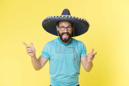 Photo for Celebrate traditions. Man on smiling face in sombrero hat celebrating, yellow background. Guy with beard looks festive in sombrero. Fest and holiday concept. Man in festive mood at party celebrating. - Royalty Free Image