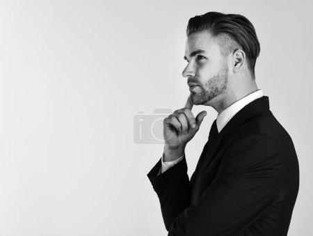 Photo pour Notion de prise de décisions. Homme en costume ou homme d'affaires avec le visage pensif sur fond gris, espace de la copie. Jeune et beau homme mal rasé touchent son menton avec index. - image libre de droit