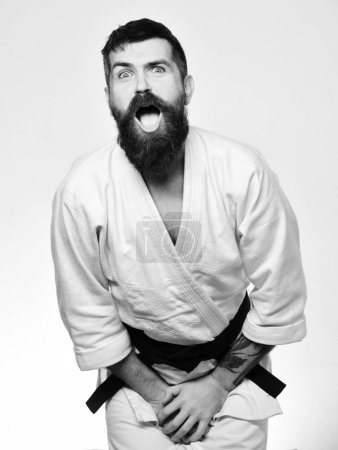 Photo for Karate man with suffering face in uniform. Man with beard in white kimono on white background. Training and combat concept. Jiu Jitsu master got punch into groin covering it with hands. - Royalty Free Image