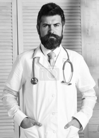 Photo for Doctor in white medical coat. Physician with confident face ready to diagnose. Medical education and examination concept. Man in surgical uniform with stethoscope on neck on wooden background. - Royalty Free Image