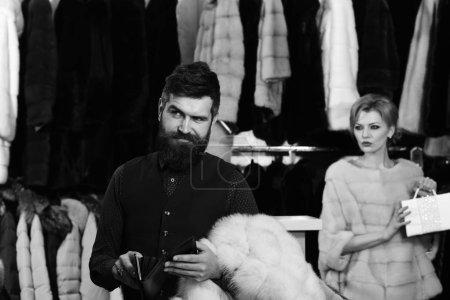Photo pour Dame et homme à barbe sur fond de manteaux de fourrure. Femme en manteau de fourrure rose avec homme dans la boutique. Concept d'achat et de la mode. Couple amoureux: fille avec le maquillage en manteau de fourrure de vison luxe et homme avec pochette. - image libre de droit