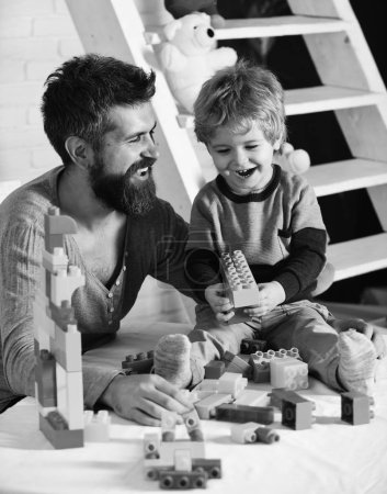 Photo for Dad and kid with ladder on background build of plastic blocks. Family and childhood concept. Man and boy play together. Father and son with happy faces create colorful constructions with toy bricks. - Royalty Free Image