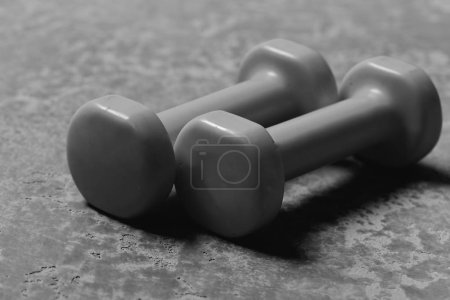Photo for Barbells placed parallelly, close up. Sports and healthy lifestyle concept. Dumbbells made of bright pink plastic on grey texture background. Shaping and fitness equipment - Royalty Free Image