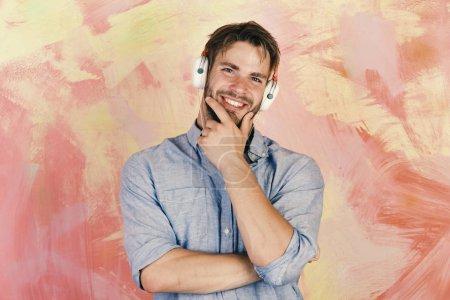 Photo pour Joyeux adolescent DJ écouter des chansons via des écouteurs. Les Européens s'amusent bien. Style de vie musical. Hipster élégant aux yeux bleus avec smartphone. Américain beau barbu gars avec écouteurs . - image libre de droit
