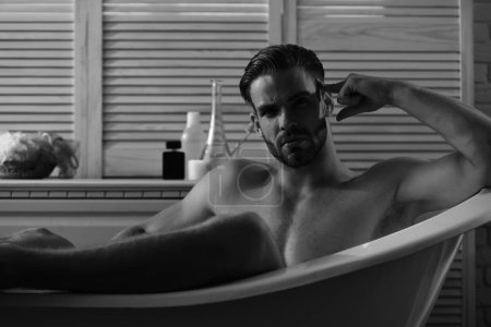 Photo for Sex and erotica concept. Macho sitting naked in bathtub with red lights on. Man with beard and serious face. Guy in bathroom with toiletries on background, selective focus. - Royalty Free Image