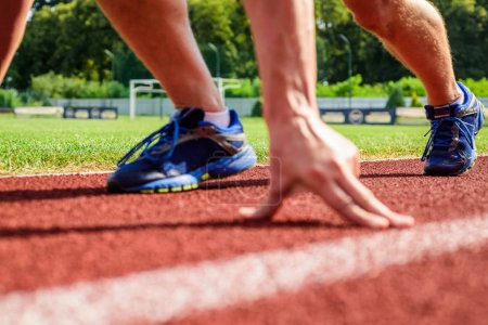 Photo for Starting point. Runner ready to go close up. Ready steady go concept. At the beginning of great sport career. Hand touch track path close up. Hand of sportsman on running track low start position. - Royalty Free Image