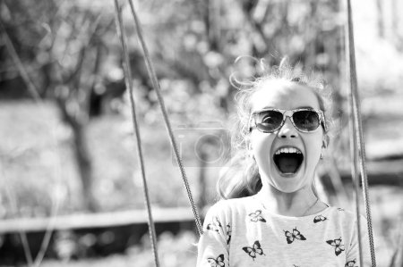 Photo for Little child smile on swing in summer yard. Fashion girl in sunglasses enjoy swinging on sunny day. Beauty kid smiling on playground. Happy childhood concept. Freedom carefree lifestyle and fun. - Royalty Free Image