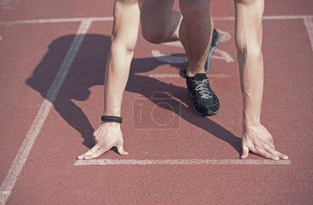 Photo pour Runner homme, mec athlétique avec musculaires mains et les jambes commencent sur la piste de course ou tapis de course dans des chaussures de mode noir ensoleillés extérieur. activité d'été et des sports. mode de vie sain, compétition, défi - image libre de droit