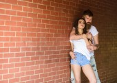He will never let her go. Couple in love hugs brick wall background. Couple find place to be alone. Girl and hipster romantic date intimacy moment. Couple enjoy intimacy cuddling without witnesses