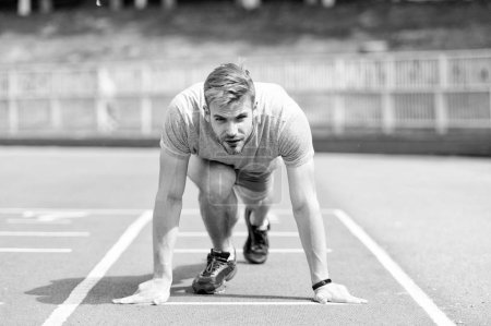 Photo for Man runner on start position at stadium. Runner in start pose on running surface. Man run outdoor at running track. Sport and athletics concept. Sportsman on concentrated face ready to go. - Royalty Free Image