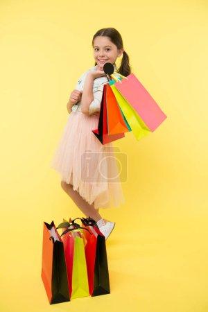 Photo pour Préparez-vous pour la saison scolaire acheter des fournitures vêtements de papeterie à l'avance. Magnifiques achats scolaires. Retour à la saison scolaire grand moment pour enseigner les bases de la budgétisation enfants. Fille porte des sacs à provisions. - image libre de droit
