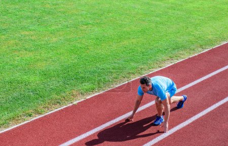 Athlete runner prepare to race. Joint mobility exercises to improve flexibility and function. Running tips for beginners. Man athlete stand low start position stadium path. Runner ready to go.