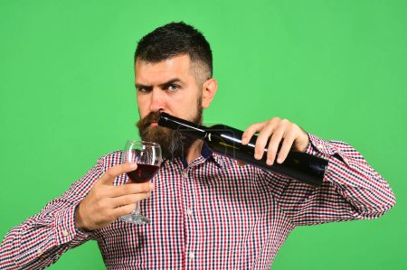 Winzer mit strengem Gesicht hält Weinglas und Flasche Wein in der Hand