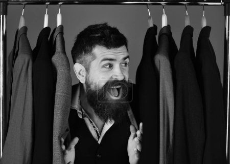 Photo for Shop assistant or seller hides among suits on clothes hangers. Businessman with happy face near jackets on blue background. Official wardrobe choice concept. Man with beard in vest by clothes rack - Royalty Free Image