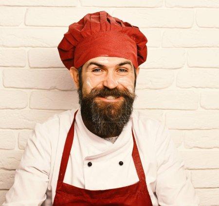 Photo pour Chef avec un large sourire. Concept des professions. Homme au visage heureux dans un fond de mur de briques blanches, gros plan. Cuire avec barbe dans un chapeau bordeaux avec de la farine sur le visage. - image libre de droit