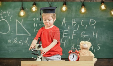 Photo for Smart kid concept. First former interested in studying, learning, education. Child on busy face near microscope. Kid boy in academic cap work with microscope in classroom, chalkboard on background. - Royalty Free Image