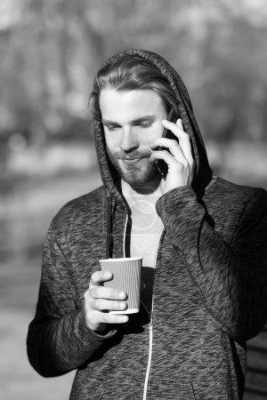 Photo pour Nouvelles technologies et la vie moderne. Mec avec smartphone et boisson à emporter sur l'air frais. Homme barbu dans le capot tenir tasse à café jetable sur ensoleillé extérieur. Ambiance de café ou de thé. Thé du matin pour le petit déjeuner. - image libre de droit