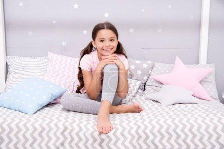 Photo pour Tiens ses douces rêves. Petite fille s'asseoir sur lit de sa chambre. Kid se préparer à aller au lit. Agréable moment relax confortable chambre à coucher. Jeune fille kid long cheveux mignon pyjama relaxant avant de dormir. Temps de sommeil ou de la sieste. - image libre de droit