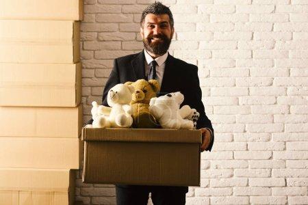 Photo pour PDG détient boîte pleine de jouets sur fond de mur blanc. Homme à la barbe et au visage souriant fait un don. Concept d'entreprise et de volontariat. Homme d'affaires porte costume intelligent et cravate, espace de copie . - image libre de droit