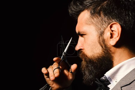 Photo for Barbershop advertising concept. Macho in formal suit cuts beard and moustache. Man with long beard holds steel scissors. Businessman with strict face isolated on black background. - Royalty Free Image