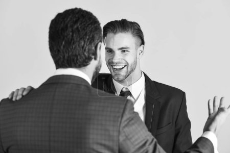 Photo for Business and friendship concept. Successful negotiations between businessmen. Boss and employee speaking at meeting on light background. Man with happy face in jacket listening his business partner. - Royalty Free Image