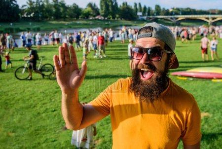 Photo pour Fête de l'événement urbain. Hipster en bonnet heureux de rencontrer un ami à l'événement pique-nique fest ou festival. Homme barbu hipster en face de la foule les gens agitant main verte fond riverain. Enchanté. . - image libre de droit
