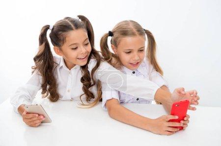 Photo pour Relâche scolaire pour les heureuse petites filles à l'aide de smartphones. petites filles à l'aide de smartphones sur relâche scolaire s'amuser - image libre de droit
