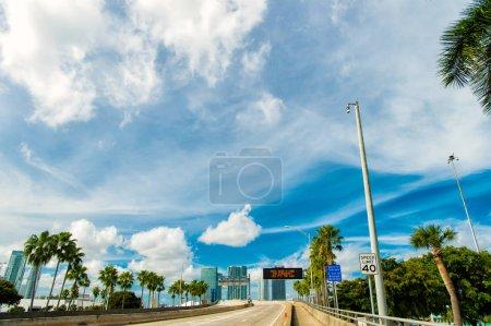 carretera con rascacielos en el cielo azul nublado