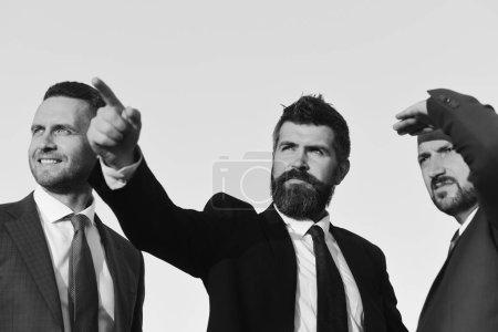Photo pour Homme à la barbe et au visage sérieux. Les managers portent des costumes intelligents, des cravates sur fond bleu ciel. Concept d'entreprise et de réussite. Les hommes d'affaires attendent avec impatience, discuter du plan. - image libre de droit