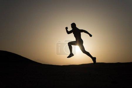 Photo pour Ne t'arrête jamais. Silhouette homme mouvement courant devant le coucher du soleil fond du ciel. Le succès futur dépend de vos efforts maintenant. Motivation quotidienne. Style de vie sain réalisations personnelles buts et succès . - image libre de droit