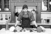 """Постер, картина, фотообои """"Кука стенд на кухонный стол. Человек в шляпе шеф-повар и фартук на кухне. Овощи и инструменты готовы для приготовления блюд. Вегетарианское меню и здоровое питание. Приготовление пищи и кулинарные рецепты"""""""