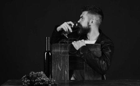 Degustator lehnt sich an Stuhl mit Weinflasche und dunklen Trauben