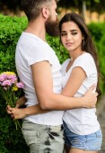 Man fall in love with gorgeous girl. Strong romantic feelings become true love. He will never let her go. Couple in love hugs on date in park green bushes background. Man bearded hipster hugs woman