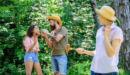 Photo for Friends eating roasted food picnic. Girl with great appetite eats roasted food. Hungry tourists eating picnic. Man feeding hungry lady with sausage. Fresh air nature conditions causes great appetite. - Royalty Free Image