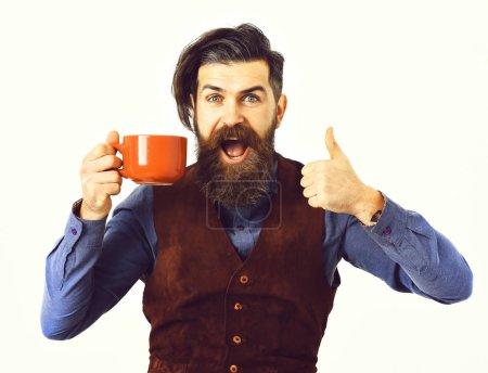 Photo pour Homme barbu, longue barbe, brutal hipster caucasien avec moustache tenant tasse ou tasse avec café, thé au visage heureux isolé sur fond blanc - image libre de droit