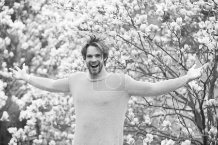 Photo for Guy in yellow sweater with open hands on floral background. Flourishing, nature, growth. Spring season concept. Man smile in park with blossoming trees. New life and optimism. - Royalty Free Image