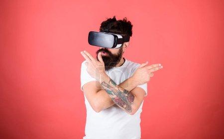 Photo pour Galerie de tir VR. Homme hipster barbu avec casque de réalité virtuelle sur fond rouge. geste de la main de l'homme comme jeu de tir à l'arme à feu dans des lunettes VR. Le tireur à la première personne montre à quel point la VR peut être addictive . - image libre de droit