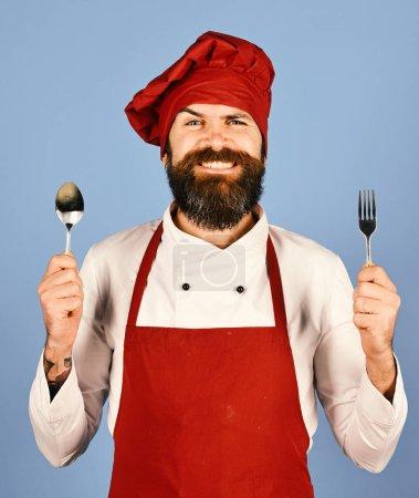 Photo pour Homme à la barbe tient ustensiles de cuisine sur fond bleu. Chef tient des couverts. Concept de cuisine professionnelle. Cuire avec le visage heureux dans un chapeau bordeaux et tablier tient cuillère et fourchette . - image libre de droit