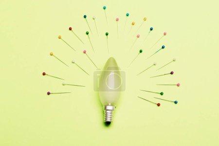 Photo pour Abstraction, idée et concept artistique. Ampoule sous forme ovale comme centre de composition. Broches de différentes couleurs placées autour de la lampe électrique sur fond vert. Les broches à coudre représentent des rayons de lumière . - image libre de droit