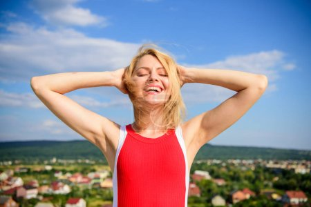Photo for Girl pleased with warm sunlight looks relaxed blue sky background. Woman blonde relaxing outdoors confident perspirant. Enjoy life without sweat smell. Dry armpit summer goal. Take care skin armpit. - Royalty Free Image