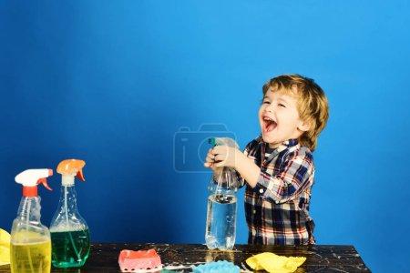 Photo pour Petit concept d'aide des parents. Garçon en chemise à carreaux sur fond bleu. Le gamin au visage riant tient le spray sur la table. Enfant près de la table en bois avec des fournitures de nettoyage sur . - image libre de droit