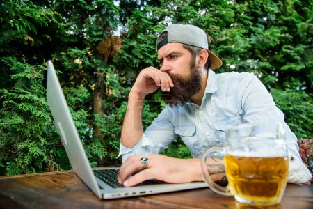 Photo pour Paris et jeux d'argent réel. Brutal homme loisir avec de la bière et jeu de sport. Fan de football barbu faire hipster parier sport jeu portable. Parier sur le Championnat du monde. Guy s'asseoir à la terrasse à l'extérieur avec de la bière. - image libre de droit