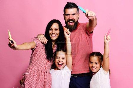 Photo pour Parents et enfants peignent avec des marqueurs et sourient. Artistes famille câlins sur fond rose. Loisirs en famille et concept d'art. Filles, homme et femme avec des visages joyeux par leur bureau d'art - image libre de droit