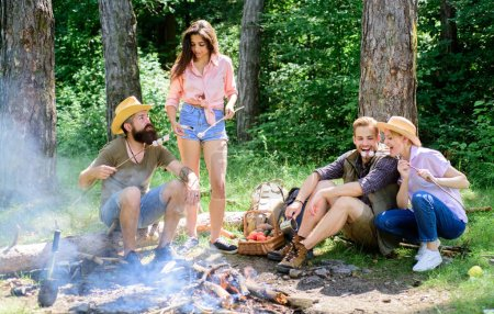 Photo for Summer vacation. Pleasant weekend near campfire. Friends couples enjoy vacation or weekend forest. Friends spend leisure weekend forest nature background. Company adult friends relaxing near campfire. - Royalty Free Image