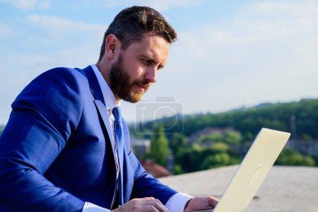 Photo pour Comment obtenir des taux de réponse élevés. Augmenter les taux de vente en ligne conseils. Homme d'affaires surfer sur Internet ou répondre aux e-mails tout en étant assis avec ordinateur portable à l'extérieur. Gestionnaire de marketing Internet fonctionne fond bleu ciel . - image libre de droit