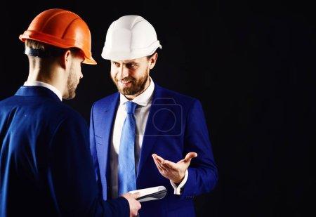 Photo pour Technicien en casques et superviseur. Inspecteur en bâtiment avec sourire visage parle à l'architecte. Construction et site heureux du dispositif avec un plan de construction. D'inspection, de soutien, de concept d'architecture. - image libre de droit