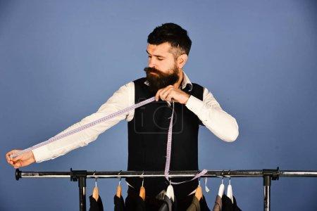 Photo pour Tailleur avec le visage occupé détient ruban à mesurer près des vestes sur fond bleu. Mode d'affaires et concept de couture. Homme avec barbe par porte-vêtements. Designer prend des mesures près de cintres avec des costumes - image libre de droit