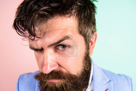 Keep hair tidy and care about hairstyle. Man bearded hipster on strict face pink blue background. Barber tips grooming beard. Hipster guy with messy tousled hair and long beard needs barber service