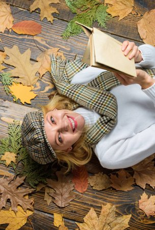 Photo pour Fille blonde poser fond en bois avec des feuilles. Elle aime le genre détective. Femme dame à carreaux chapeau et écharpe lire le livre. Fille en tenue vintage profiter de la littérature. Que lire dans la liste des livres d'automne . - image libre de droit